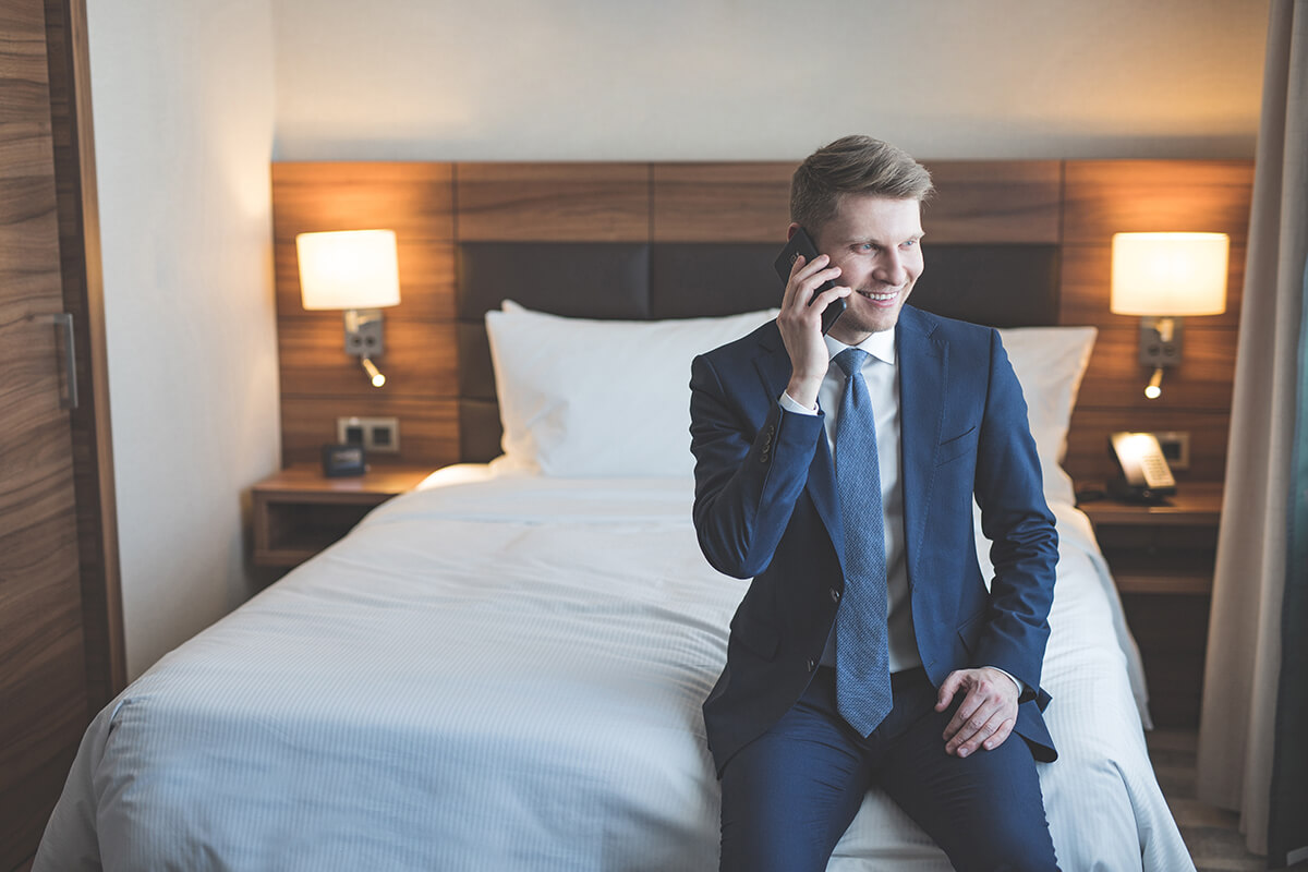 Smiling man talking on a phone in the hotel