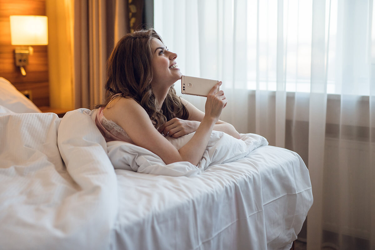 Dreaming young girl with a phone in room